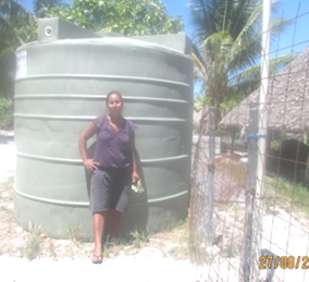 The Maiana Clerk, Terainamn, posing near a water tank at Toora village.